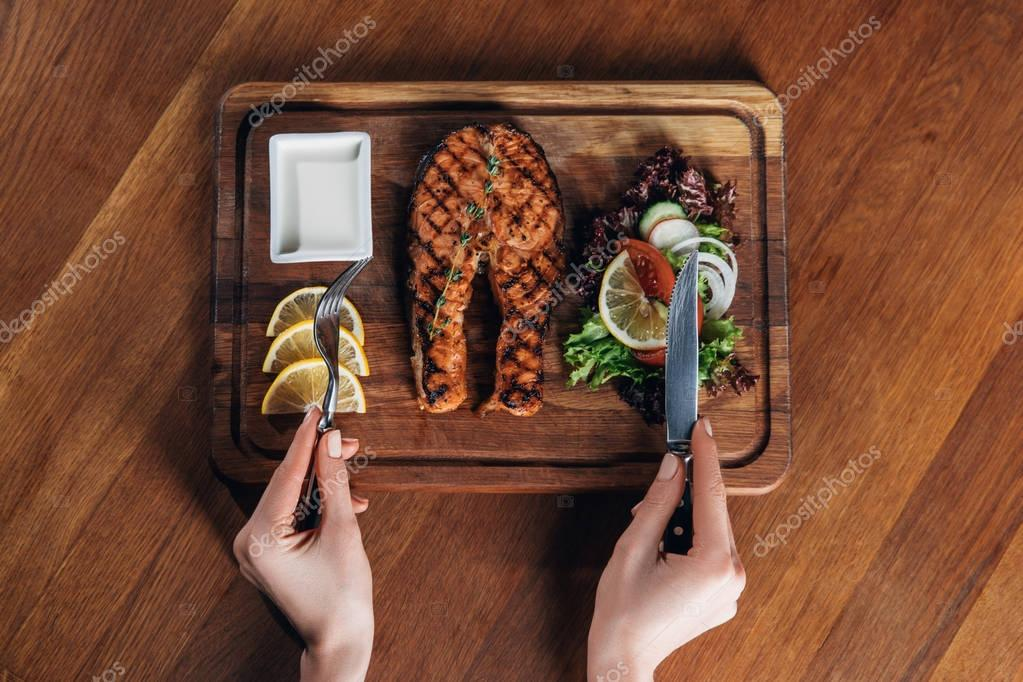 cropped shot of woman eating grilled salmon steak served on wooden board with lemon and lettuce