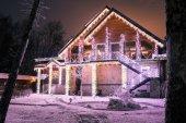 Fotografie dřevěný dům s girlandami večer v lese