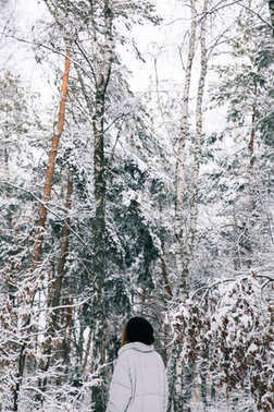 back view of woman walking in snowy forest