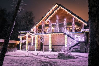 wooden house with garlands in evening in forest