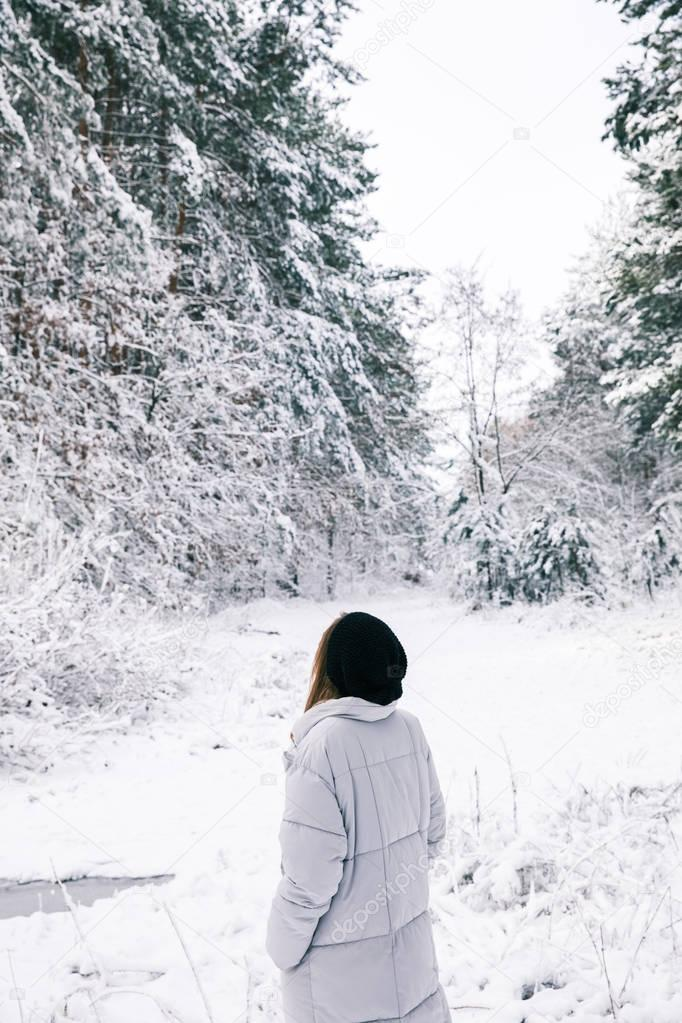 rear view of woman walking in snowy forest