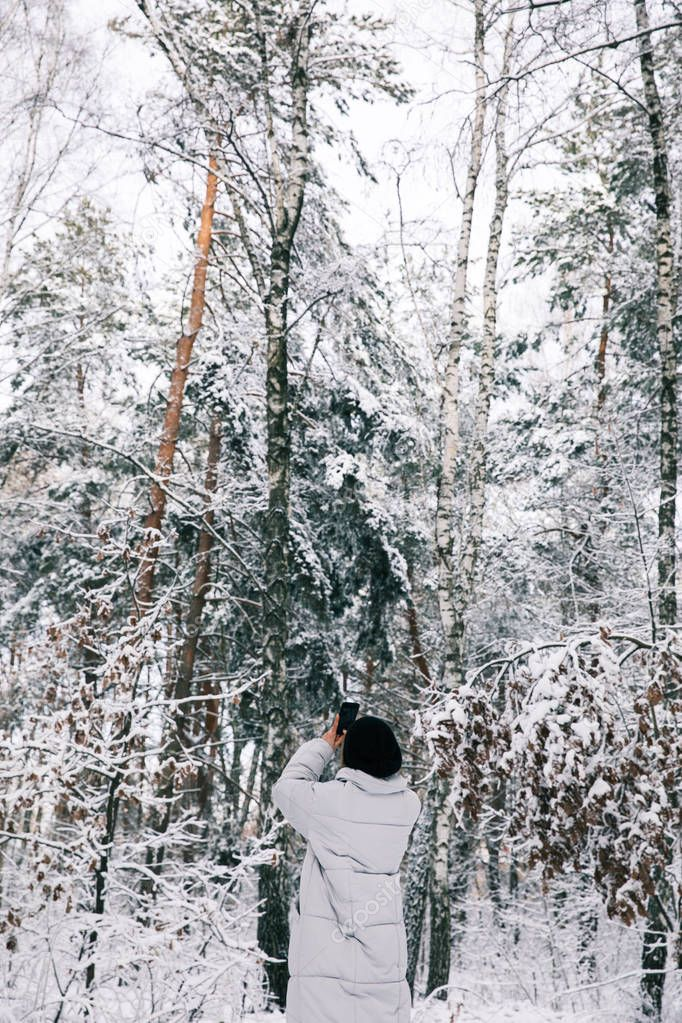 back view of woman taking photo of snowy forest by smartphone