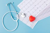 Fotografie stethoscope, cardiogram and red heart isolated  on blue background