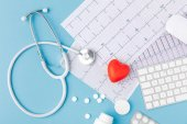 Fotografie stethoscope, paper with cardiogram, scattered pills, red heart and keyboard isolated on blue background