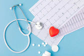 stethoscope, paper with cardiogram, scattered pills and red heart isolated  on blue background