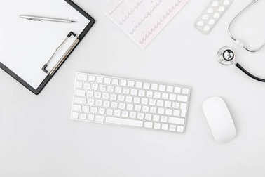 keyboard surrounded by paper in folder, computer mouse, stethoscope isolated on white background