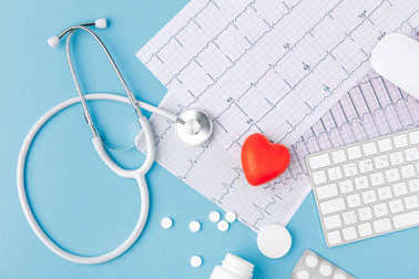 Stethoscope, paper with cardiogram, scattered pills, red heart and keyboard isolated on blue background stock vector