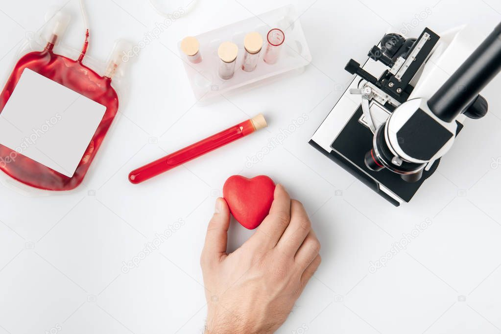 top view of hand holding red heart against vials with blood and microscope isolated on white background