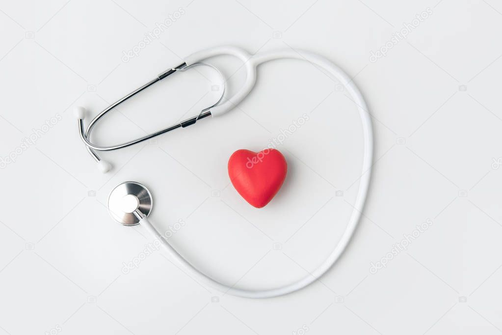 stethoscope with red heart laying isolated on white background