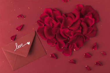 top view of heart made of roses petals and envelope isolated on red, st valentines day concept