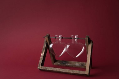 two empty heart shaped glass jars on wooden stand on red