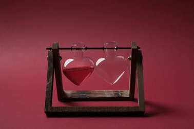 heart shaped glass jar with perfume and empty glass jar on wooden stand on red