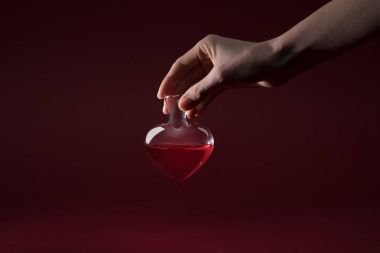 cropped image of woman holding heart shaped glass jar of love potion isolated on red