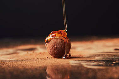 close up view of pouring caramel onto truffle process on black