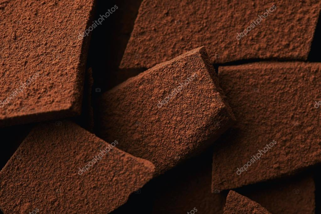 close up view of heap of chocolate bars in cocoa powder