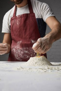 cropped image of chef preparing dough and adding egg to flour