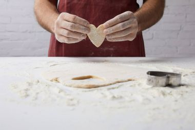 cropped image of chef holding heart shaped piece of dough in hands, valentines day concept