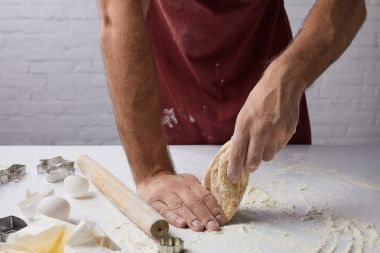 cropped image of chef preparing dough in kitchen