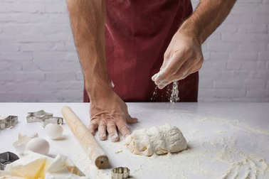 cropped image of chef adding flour to dough