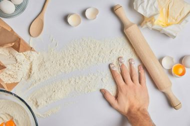 cropped image of chef putting hand on table with flour