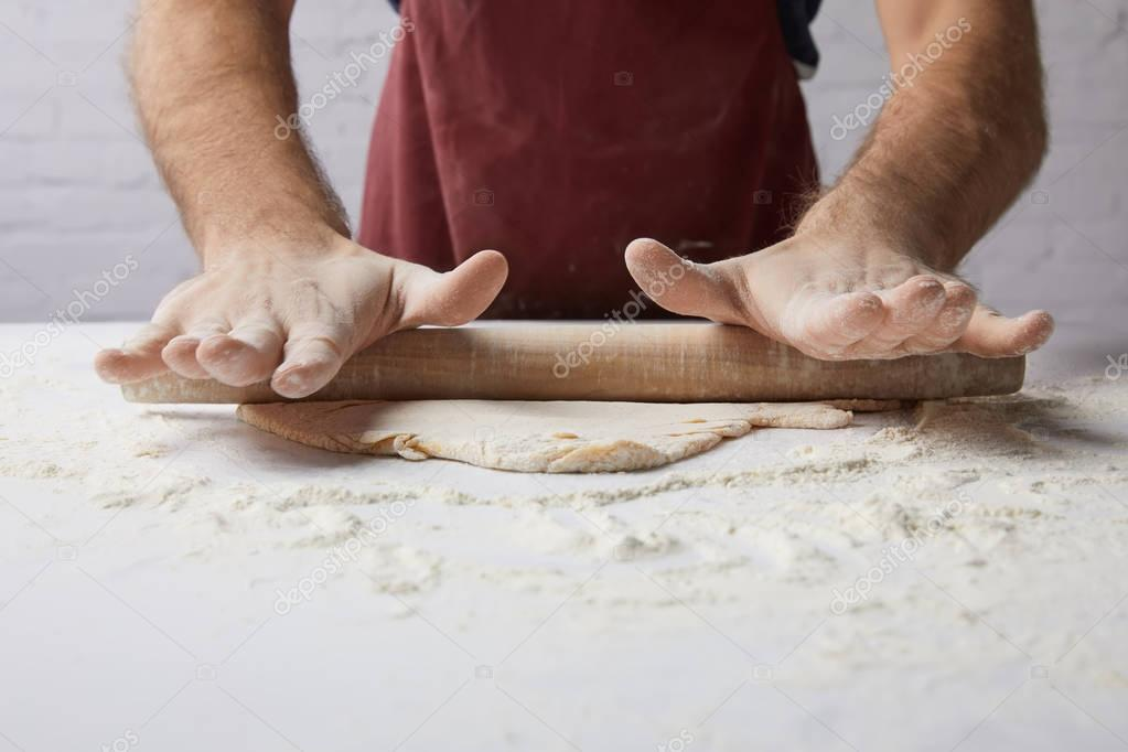 cropped image of chef rolling dough with rolling pin