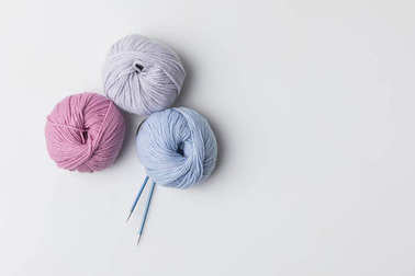 top view of colored yarn balls and knitting needles isolated on white
