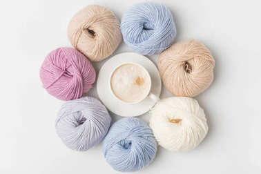top view of circle of colored yarn balls and coffee in cup on white background