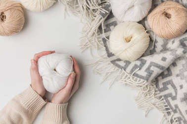cropped view of woman holding white yarn ball on white background
