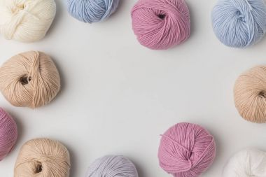 top view of scattered colored yarn balls  on white background
