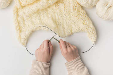 cropped view of woman knitting white wool with needles on white background