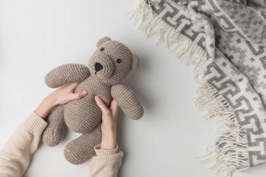cropped view of woman holding teddy bear in hands on white background