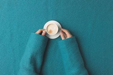 cropped view of woman hands with cup of coffee laying over turquoise fabric