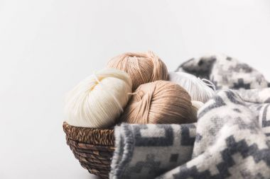 colored yarn balls in wicker basket with blanket isolated on white