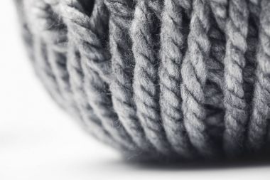 close up view of grey yarn ball on white background