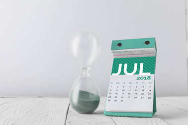 close up view of hourglass and july calendar on wooden tabletop isolated on white