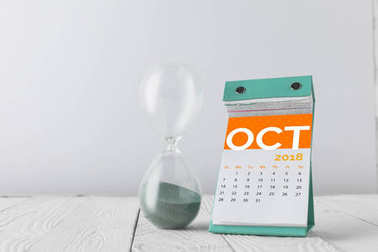 close up view of hourglass and october calendar on wooden tabletop isolated on white