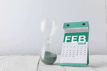 close up view of hourglass and february calendar on wooden tabletop isolated on white