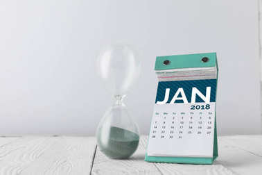 close up view of hourglass and january calendar on wooden tabletop isolated on white