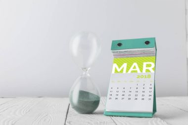 close up view of hourglass and march calendar on wooden tabletop isolated on white