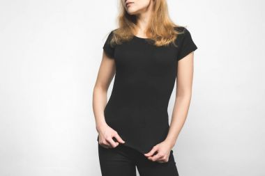 cropped shot of young woman in blank black t-shirt on white