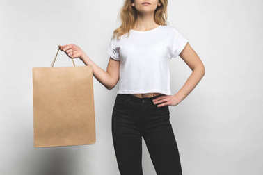 cropped shot of woman in blank t-shirt on white with shopping bag