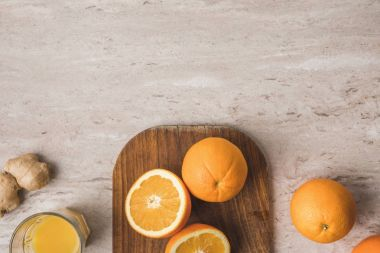 top view of oranges on cutting board on marble tabletop