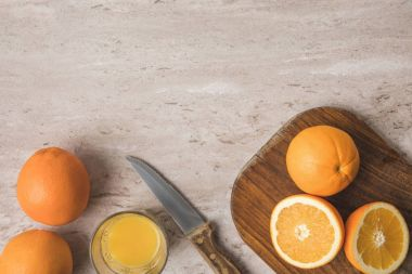 top view of oranges, knife and wooden board on marble surface