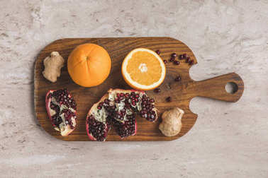 top view of oranges, pomegranate and ginger on cutting board