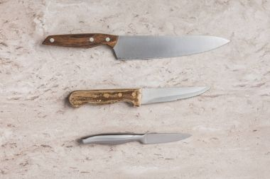 top view of three different knifes on marble tabletop