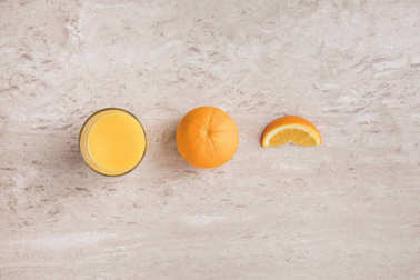 top view of glass of fresh orange juice and oranges on table