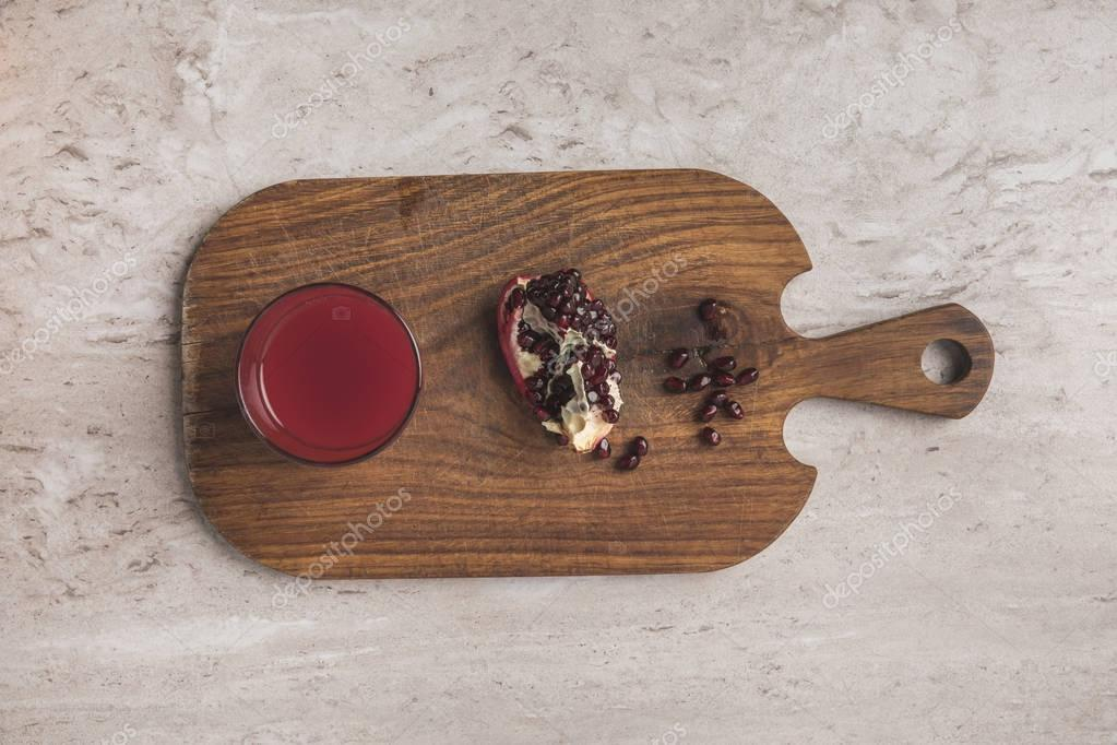 top view of homemade pomegranate juice and fruit on wooden board