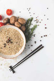 Photo top view of raw rice in bowl with mushrooms and tomatoes on white surface with chopsticks