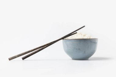 bowl of tasty rice with chopsticks on white tabletop
