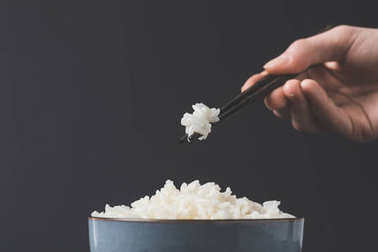 cropped shot of woman taking freshly cooked rice from bowl with chopsticks